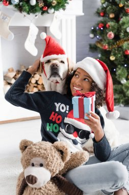Smiling african american girl stroking labrador while sitting on floor with gift box and teddy bear on blurred background stock vector