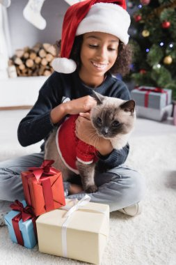 Neşeli Afrikalı Amerikalı kız Noel Baba şapkalı pofuduk kediyi kucaklarken bulanık arka planda yılbaşı hediyelerinin yanında oturuyor.