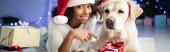 fröhliches afrikanisch-amerikanisches Mädchen zeigt mit dem Finger auf Geschenkschachtel, während sie auf dem Boden neben Labrador-Hund auf verschwommenem Hintergrund liegt, Banner