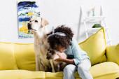 Glückliches Mädchen beugt sich und umarmt siamesische Katze, während es neben Labrador auf gelbem Sofa zu Hause sitzt