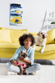 KYIV, UKRAINE - Október 02, 2020: boldog afro-amerikai lány joystick átöleli macska közel kutya feküdt kanapén otthon