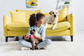 KYIV, UKRAINE - OCTOBER 02, 2020: African american girl with joystick and cat and looking at labrador on sofa at home