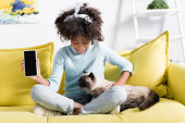 Photo Smiling african american girl showing smartphone with blank screen, looking at cat and sitting on sofa at home