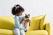 Photo Happy curly girl with headband holding and looking at siamese cat, sitting on sofa at home
