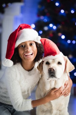 Smiling african american girl hugging labrador in santa hat on blurred background stock vector