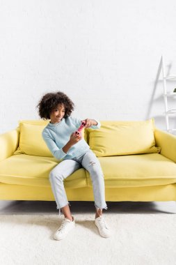 KYIV, UKRAINE - OCTOBER 02, 2020: Happy african american girl playing with pink joystick on yellow sofa at home stock vector