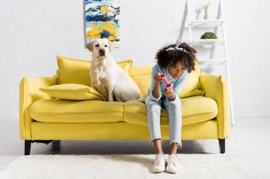KYIV, UKRAINE - OCTOBER 02, 2020: Focused african american girl bending while playing with joystick near retriever at home stock vector