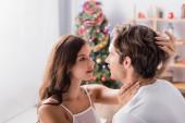 žena objímání přítel s zdobené vánoční strom na rozmazaném pozadí
