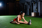 athletic sportswoman touching sneaker while doing stretching exercise in gym