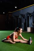 lächelnde Sportlerin mit Turnschuhen beim Stretching im Sportzentrum