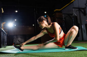 sportswoman in top and shorts reaching sneaker while doing seated side bend exercise in sports center