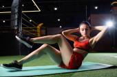 sportos nő rövidnadrágban és felül csinál térd-könyök gyakorlás fitness szőnyegen