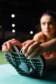 Sportlerin berührt Turnschuhe bei Stretchübung im Fitnessstudio, verschwommener Hintergrund