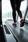 Fotografie Teilaufnahme einer Sportlerin in Turnschuhen und Leggings, die auf dem Laufband läuft