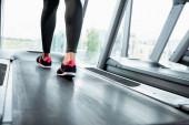 Ausgeschnittene Ansicht einer Sportlerin in Leggings und Turnschuhen beim Training auf dem Laufband