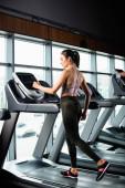 Fotografie athletische Sportlerin in Leggings beim Training auf dem Laufband im Fitnessstudio