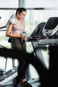 Photo tired sportswoman standing on treadmill with closed eyes and holding sports bottle on blurred foreground