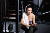 sportovkyně s ručníkem chatování na smartphone zatímco sedí na tréninkovém stroji ve sportovním centru na rozmazané popředí