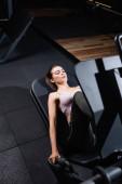 vysoký úhel pohledu sportovkyně cvičení na noze lis cvičení stroj na rozmazané popředí