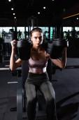 sportos nő felül és leggings dolgozik ki a fegyverhosszabbító gyakorló gép