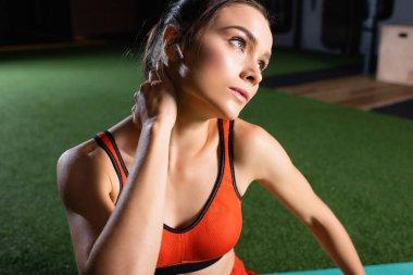 Spor merkezine bakarken kulaklığı boynunu ısıtan sporcu kadın.