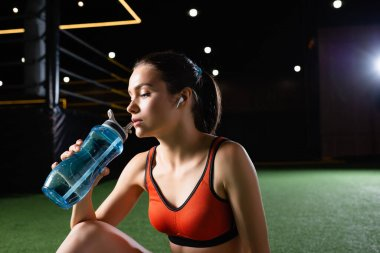 Young sportswoman drinking from sports bottle in gym stock vector