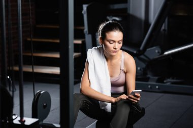 Sportswoman with towel chatting on smartphone while sitting on training machine in sports center on blurred foreground stock vector