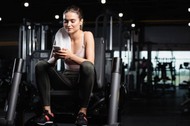 Sportswoman sitting on training machine, chatting on smartphone and listening music in wireless earphone stock vector