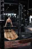 Fotografie athletic sportswoman training with power rack in sports center