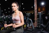 fiatal sportasszony nézi a kamerát, miközben ül és tartja súlyzók edzőteremben