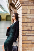 glamour woman in black lurex dress and sunglasses standing with wine bottle at underground station