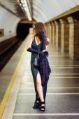 fashionable woman in long black dress standing on subway platform