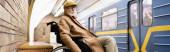 elderly disabled man in wheelchair, wearing autumn clothes, near train on subway platform, banner