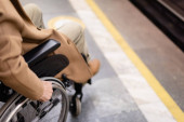 cropped view of blurred handicapped man in wheelchair on subway platform