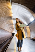 stylish woman in autumn clothes looking away while holding city map on underground platform