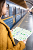 cropped view of young woman holding city map while standing near metro train on blurred foreground