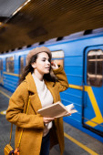 stylish woman in autumn clothes holding book while looking at blurred train on subway platform