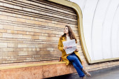 stylish woman in autumn clothes looking away while sitting on metro platform bench with newspaper