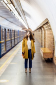 stylish woman in autumn clothes looking at train on underground platform, blurred background