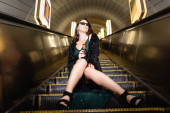 low angle view of glamour woman posing on escalator with bottle of wine