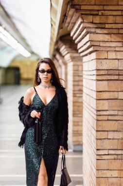 Elegant woman in black lurex dress standing with wine bottle and handbag on underground station stock vector