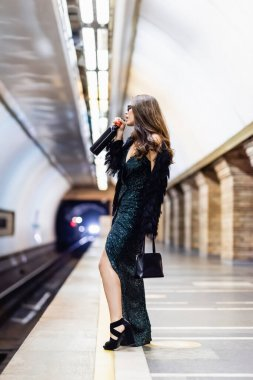 Side view of fashionable woman in long black dress drinking wine from bottle on metro platform stock vector