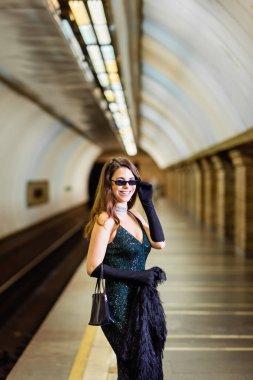 Elegant woman in black lurex dress smiling at camera on metro station platform stock vector
