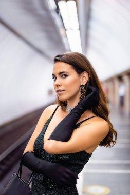 Seductive woman in elegant black dress and gloves looking at camera on subway platform stock vector