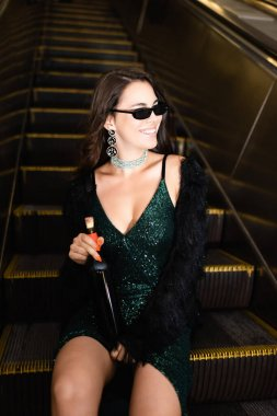 Glamour woman in sunglasses sitting on metro escalator with bottle of wine stock vector
