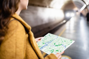 cropped view of woman holding city map on underground platform, blurred foreground