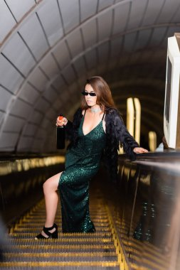 Elegant woman on escalator in long black dress and sunglasses holding wine bottle on blurred foreground stock vector