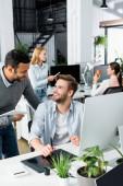 Multietničtí podnikatelé při pohledu na sebe v blízkosti grafického tabletu a počítače na rozmazaných popředí v kanceláři