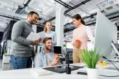 Lächelnde multikulturelle Geschäftsleute mit Geräten und Kaffee zum Reden im Büro