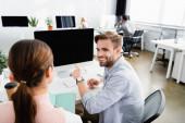 Usmívající se podnikatel ukazuje prstem na monitor počítače poblíž kolegy a kávu jít do úřadu